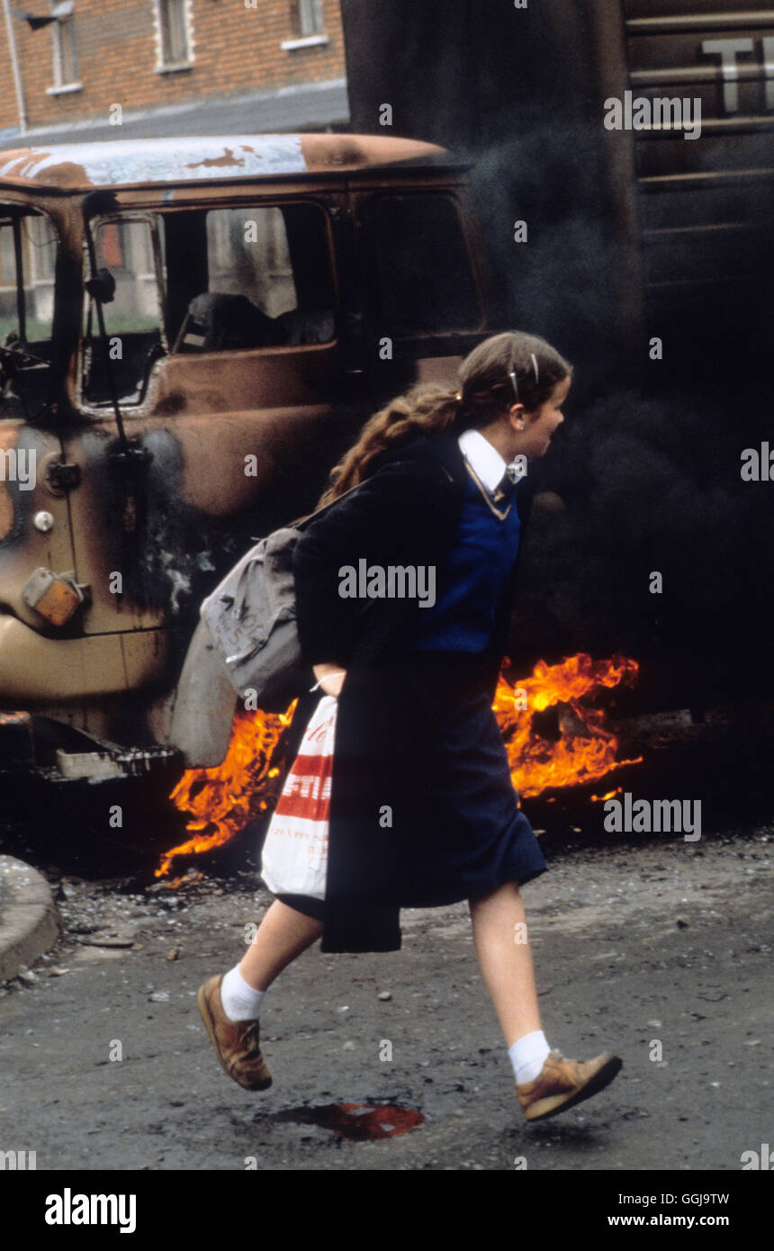 Belfast The Troubles 1980s. School girl rushes past a burning hijacked lorry used as a barricade Northern Ireland - Stock Image