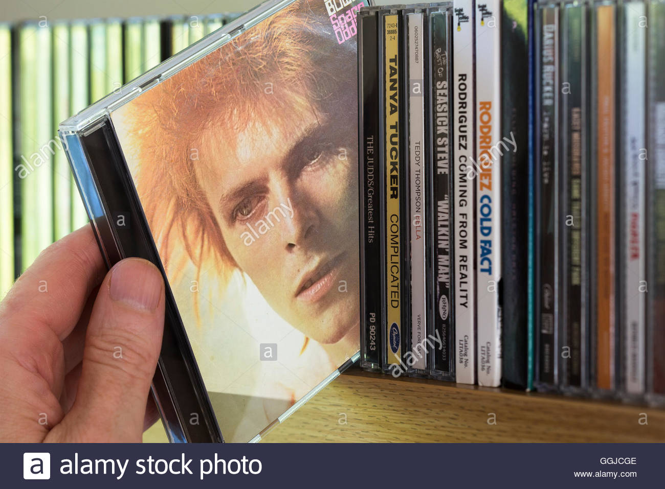 Space Oddity, 1969 David Bowie CD being chosen from a shelf of other CD's - Stock Image