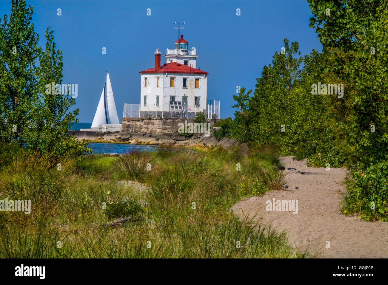 A classic Lake Erie lighthouse, The Fairport Harbor West Breakwater Light in Fairport Ohio as a sailboat passes - Stock Image