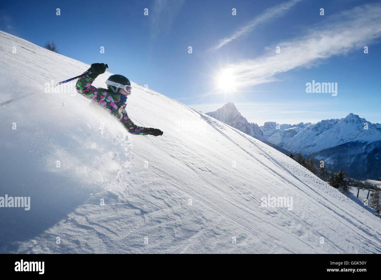 Girl downhill skiing from mount Helm (Monte Elmo), Sexten, South Tyrol, Italy - Stock Image