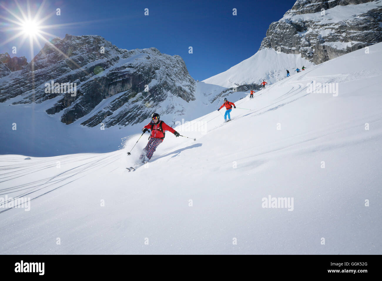 Skiers downhill skiing from mount Zugspitze, Upper Bavaria, Germany - Stock Image