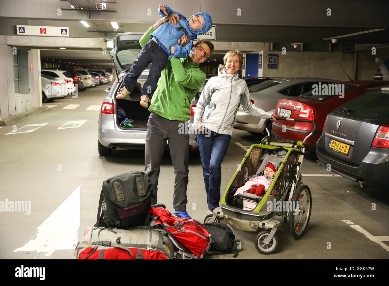 Young family with children, departure at airport, car parking area, baby, small boy, luggage, stroller, backpack, - Stock Image