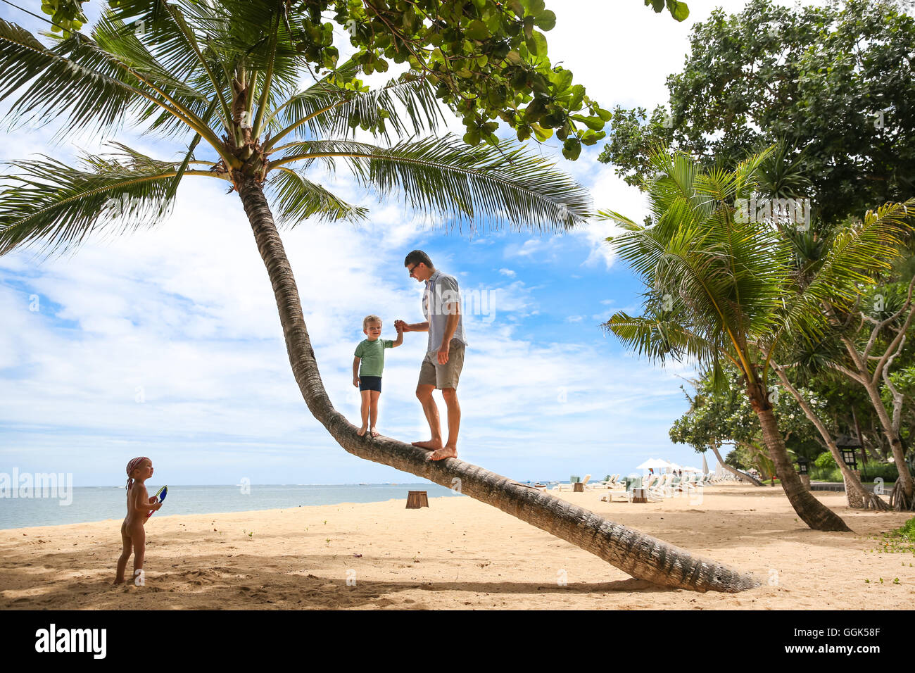 Father and son standing on a coconut tree, beach, little boy 3 years old, western family, family travel in Asia, - Stock Image