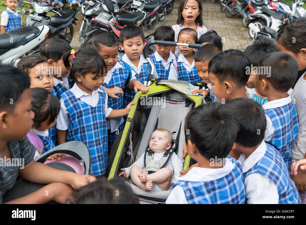 Many Balinese schoolchildren being curious about western baby, girl 5 months old, sitting in a stroller, kids gathering - Stock Image