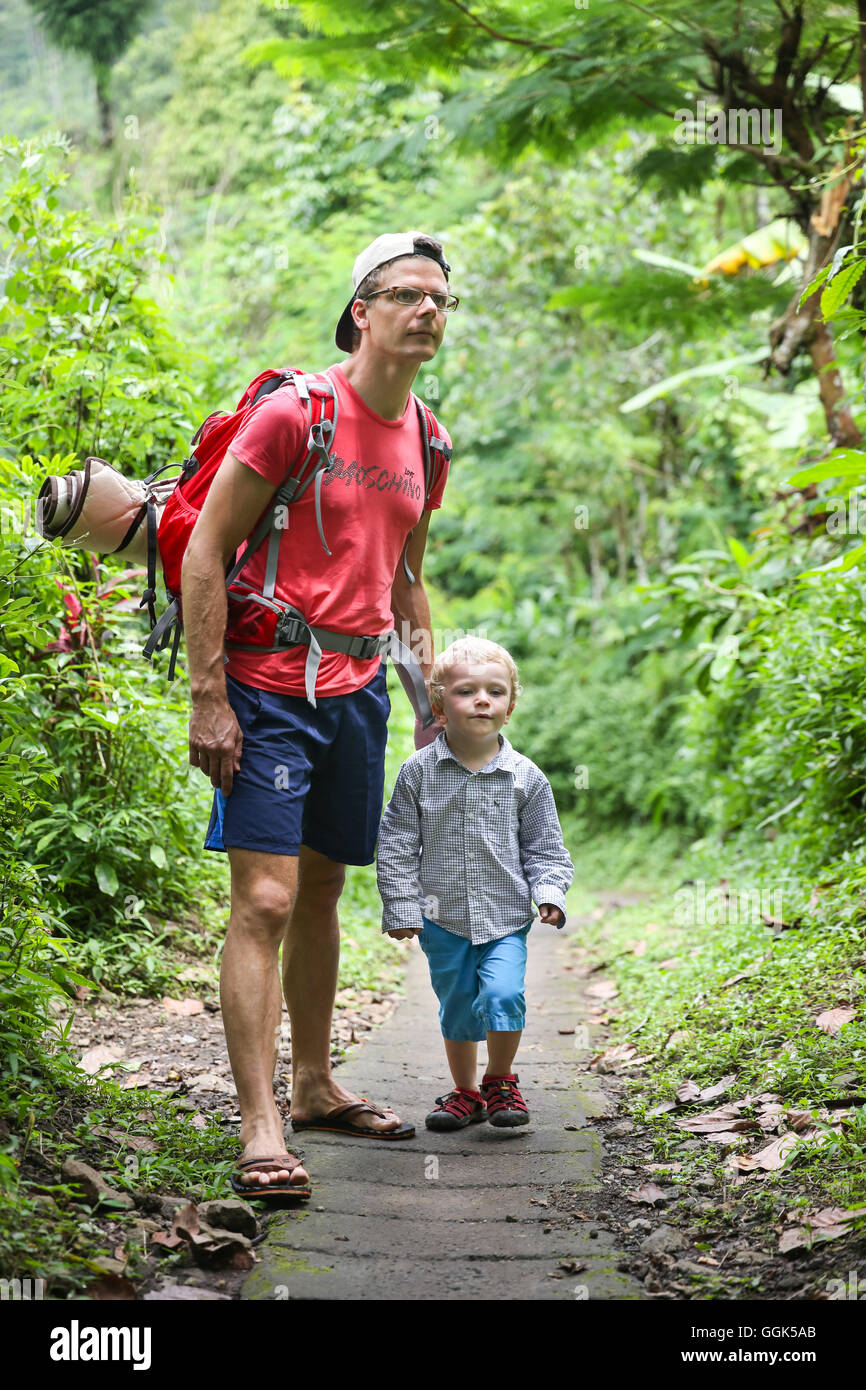 Father hiking with his son, boy 3 years old, tropical rain forest, walking, family travel in Asia, parental leave, - Stock Image