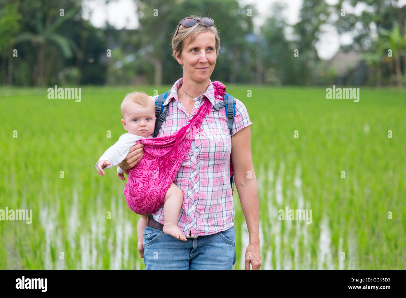 Mother with her baby, baby sling, wrap, in a rice field, paddy, smile, countryside, family travel in Asia, parental - Stock Image