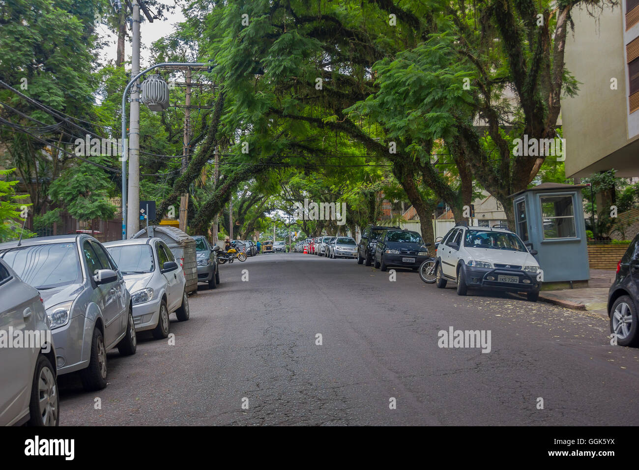 PORTO ALEGRE, BRAZIL - MAY 06, 2016: cars parked in the side of a nice street with trees in the sidewalks - Stock Image