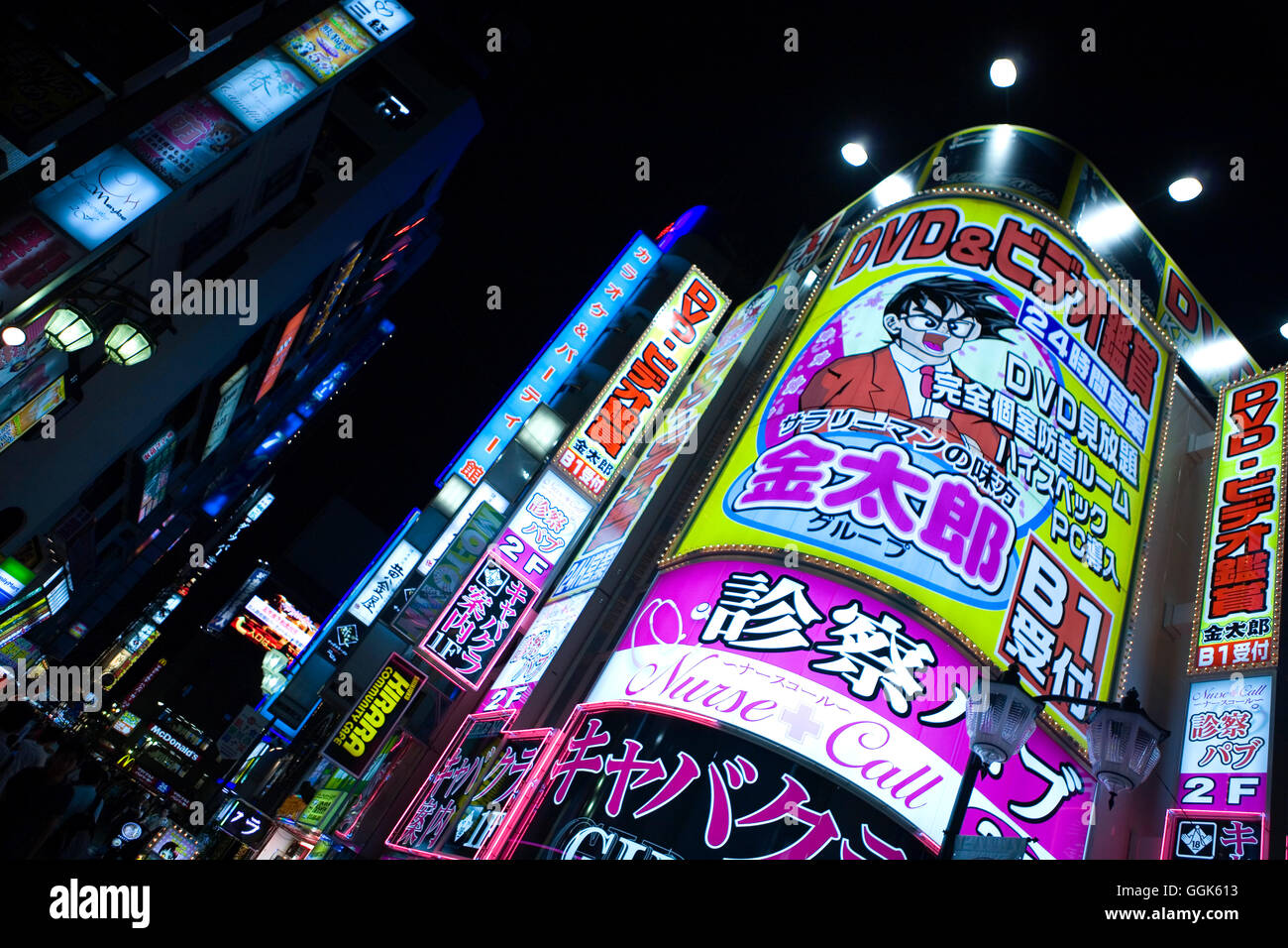 Brightly lit advertising on a busy street corner at night, Tokyo, Kanto Region, Honshu, Japan - Stock Image