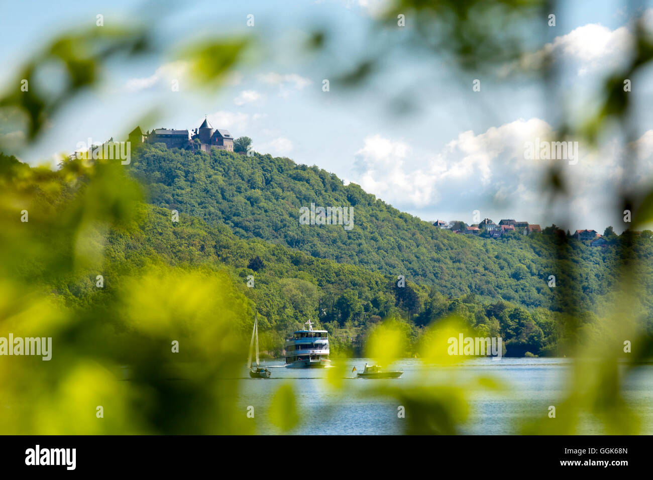 View through branches towards Waldeck Castle with excursion boat, Stern of Waldeck, on Lake Edersee in Kellerwald - Stock Image