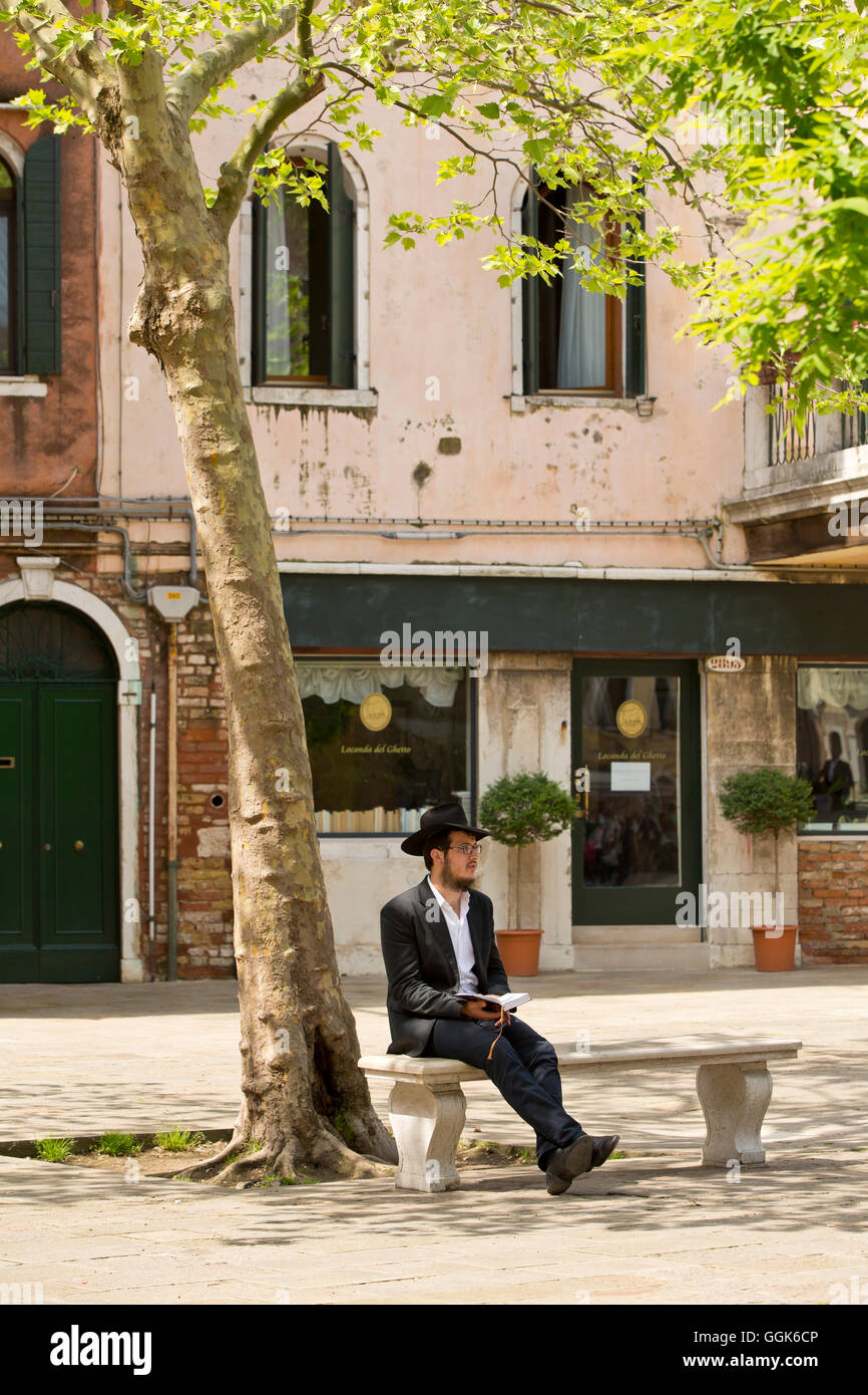 A jew sitting on a bench under a tree at Campo del Ghetto Nuovo in Ghetto Vecchio, Venice, Veneto, Italy, Europe - Stock Image