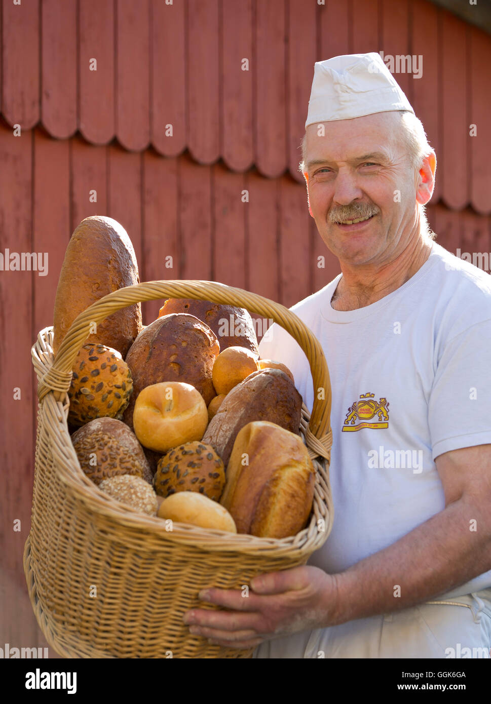 Baker Erwin Oehl with a basket of baked goods at his backery, Frankenau, Hesse, Germany, Europe - Stock Image