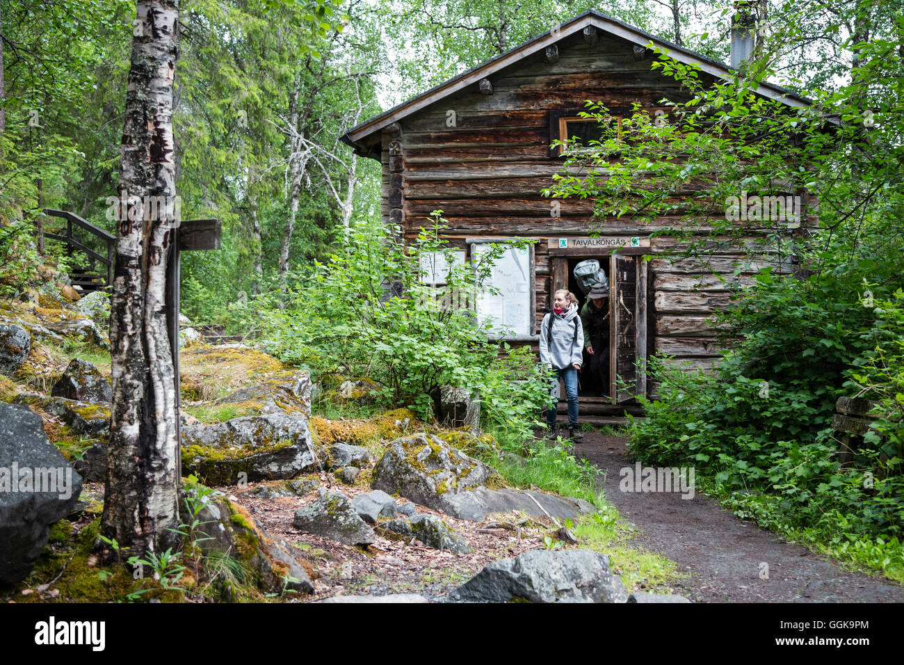 Hiker in front of hut Taivalkoengas, Karhunkierros hiking trail, Oulanka National Park, Northern Ostrobothnia, Finland - Stock Image