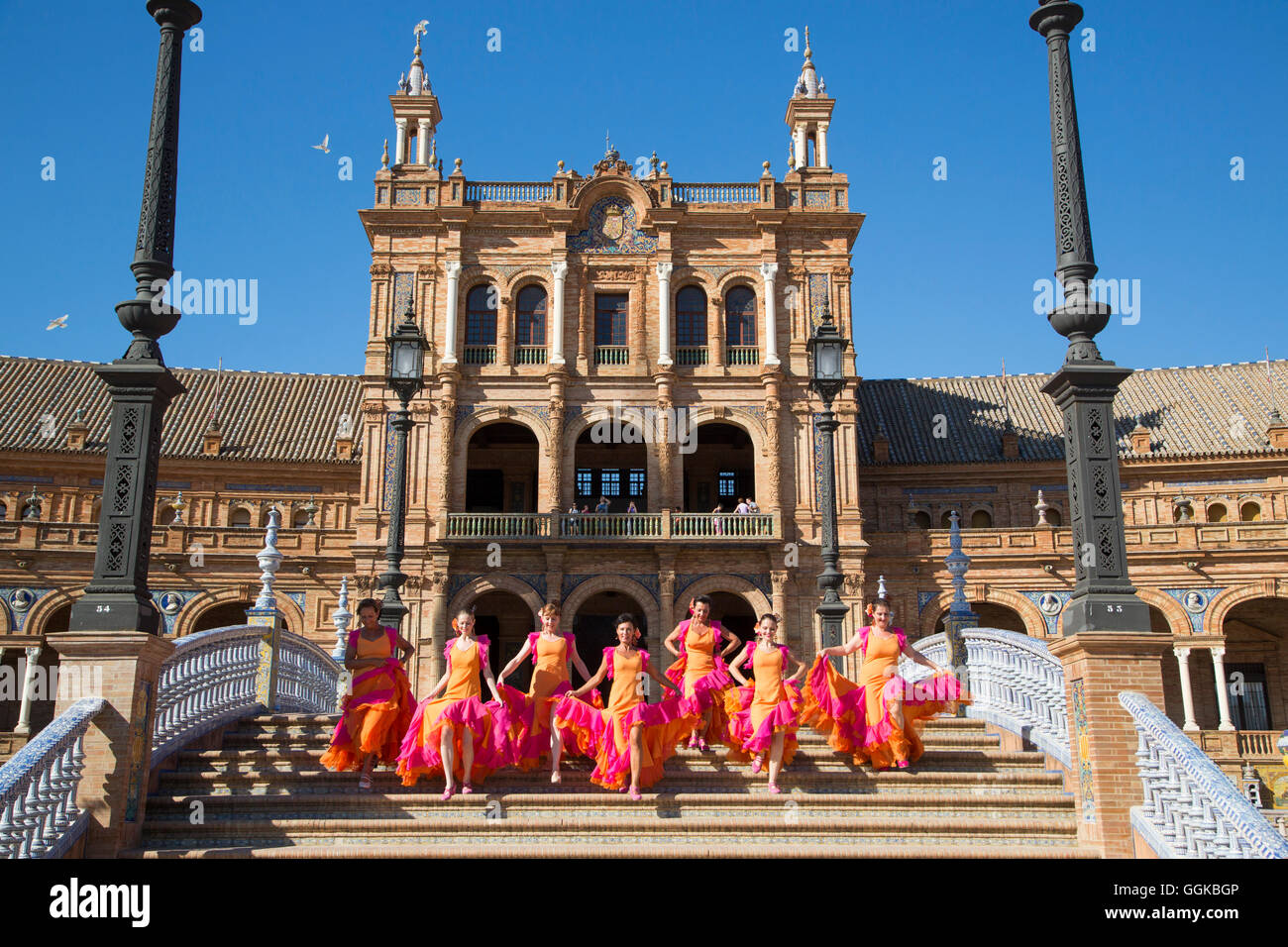 Members of Flamenco Fuego dance group running down the steps at Plaza de Espana, Seville, Andalusia, Spain - Stock Image