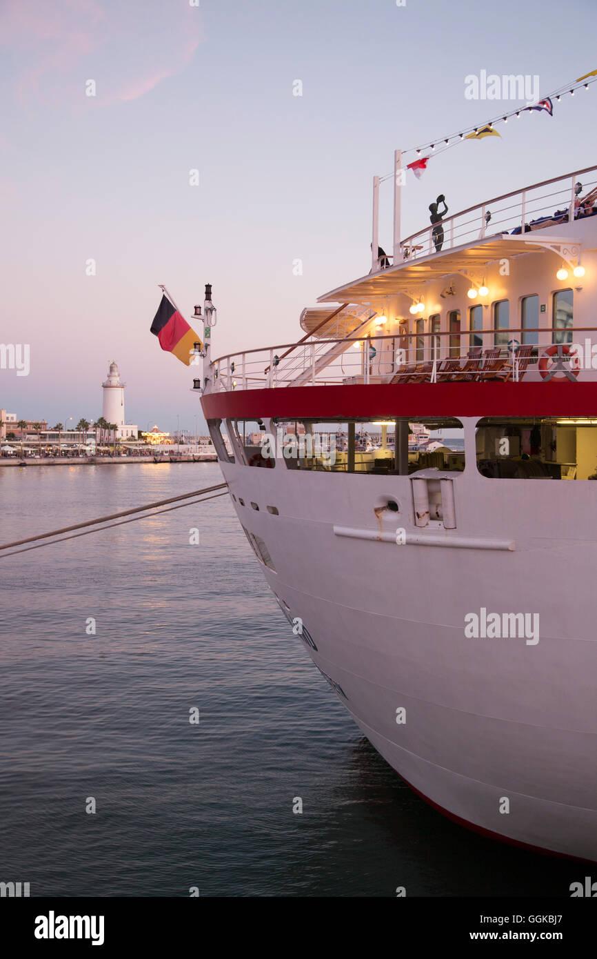 Cruise ship MS Deutschland (Reederei Peter Deilmann) and lighthouse at dusk, Malaga, Andalusia, Spain - Stock Image