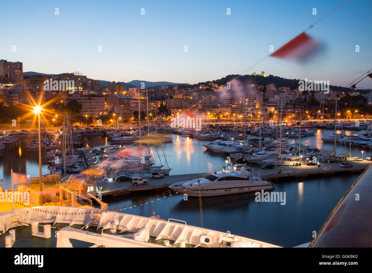 Bow of cruise ship MS Deutschland (Reederei Peter Deilmann) and sailing boats in the marina at dusk, Palma, Mallorca, - Stock Image