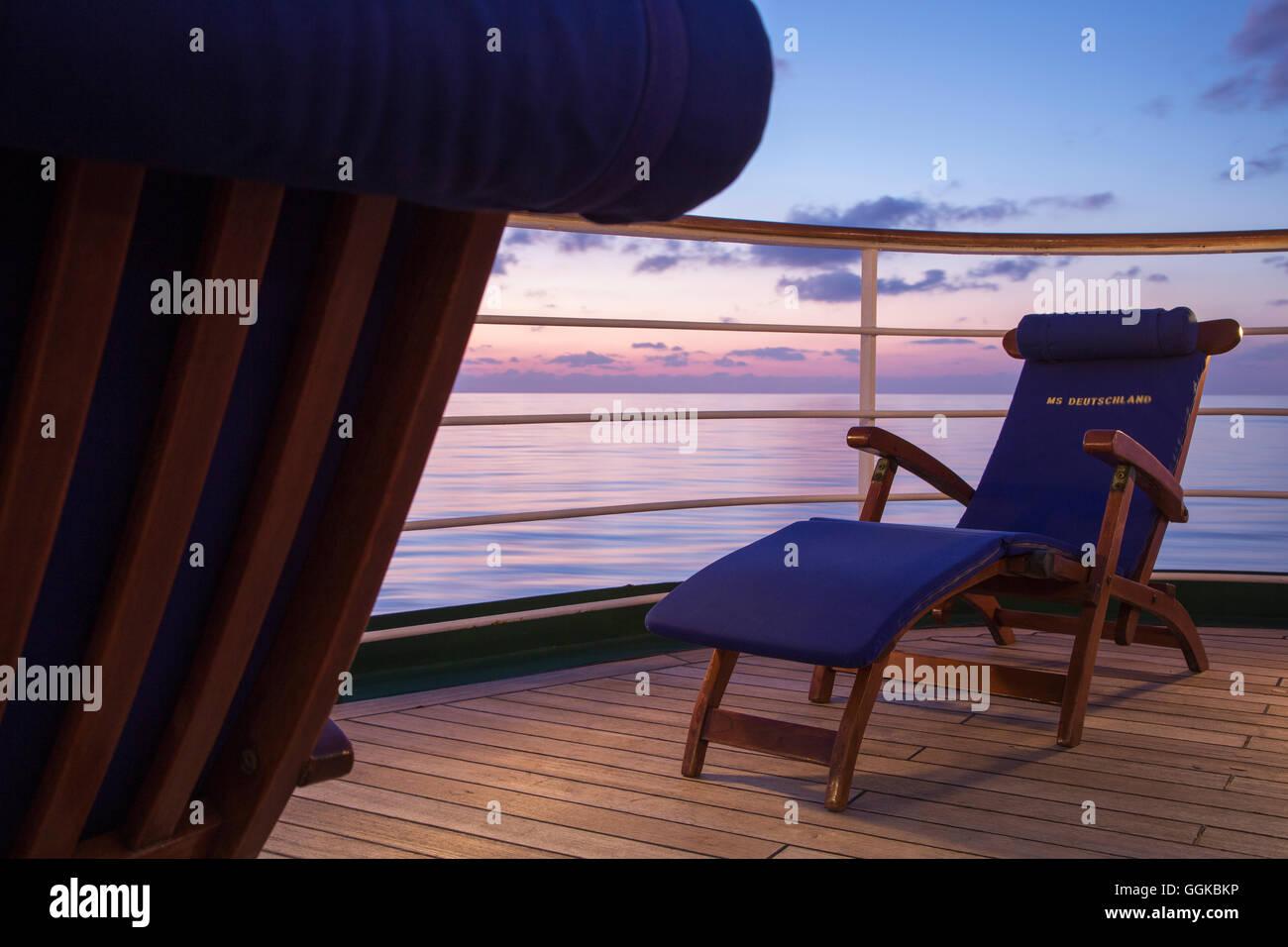 Deck chairs aboard cruise ship MS Deutschland (Reederei Peter Deilmann) at dusk, Mediterranean Sea, near Italy - Stock Image