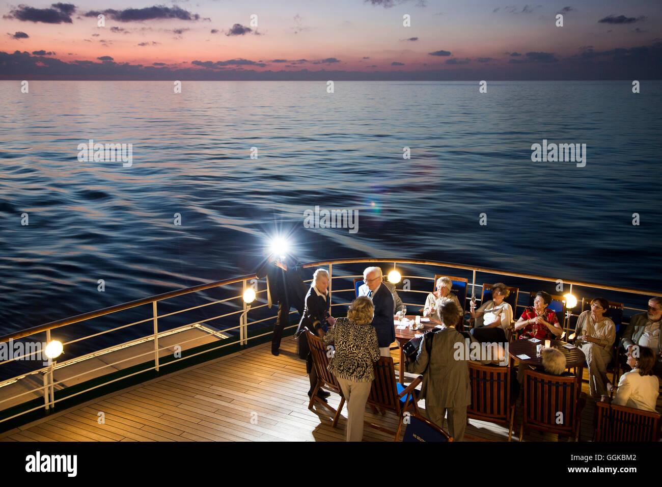 Photographer's flash illuminating birthday celebrations on the deck of cruise ship MS Deutschland (Reederei - Stock Image