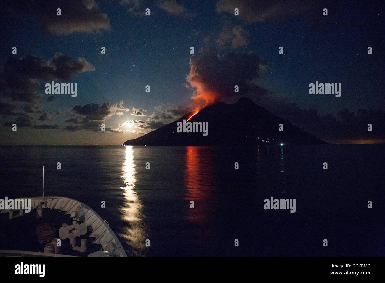Bow of cruise ship MS Deutschland (Reederei Peter Deilmann) approaching Stromboli volcano with lava flow and moonrise, - Stock Image