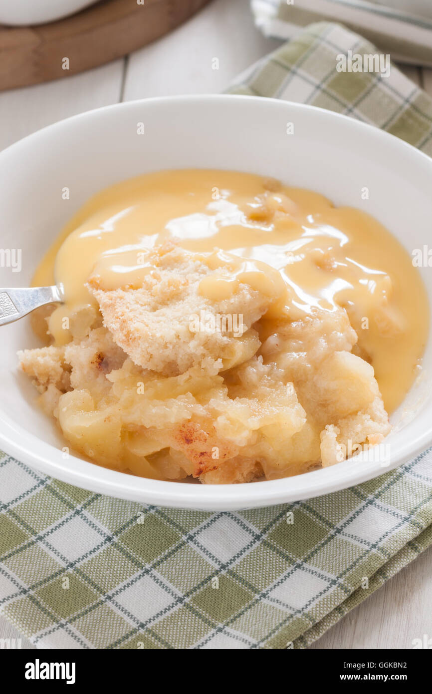 Home made apple crumble or apple cobbler with vanilla custard - Stock Image