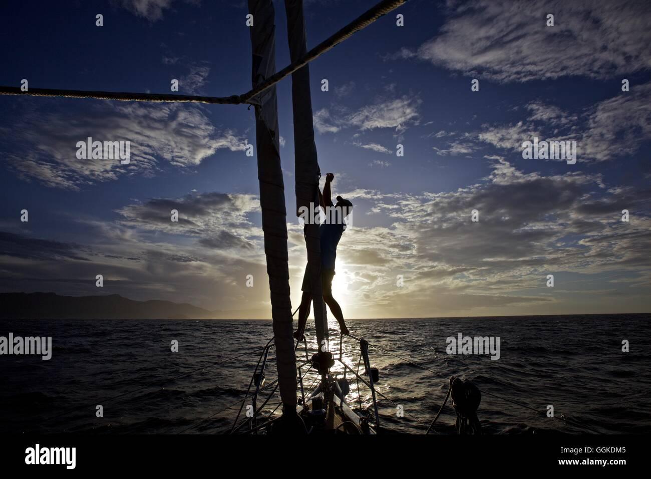 Yachtsman binding back the headsail at sunset, Genoa, Liguria, Italy - Stock Image