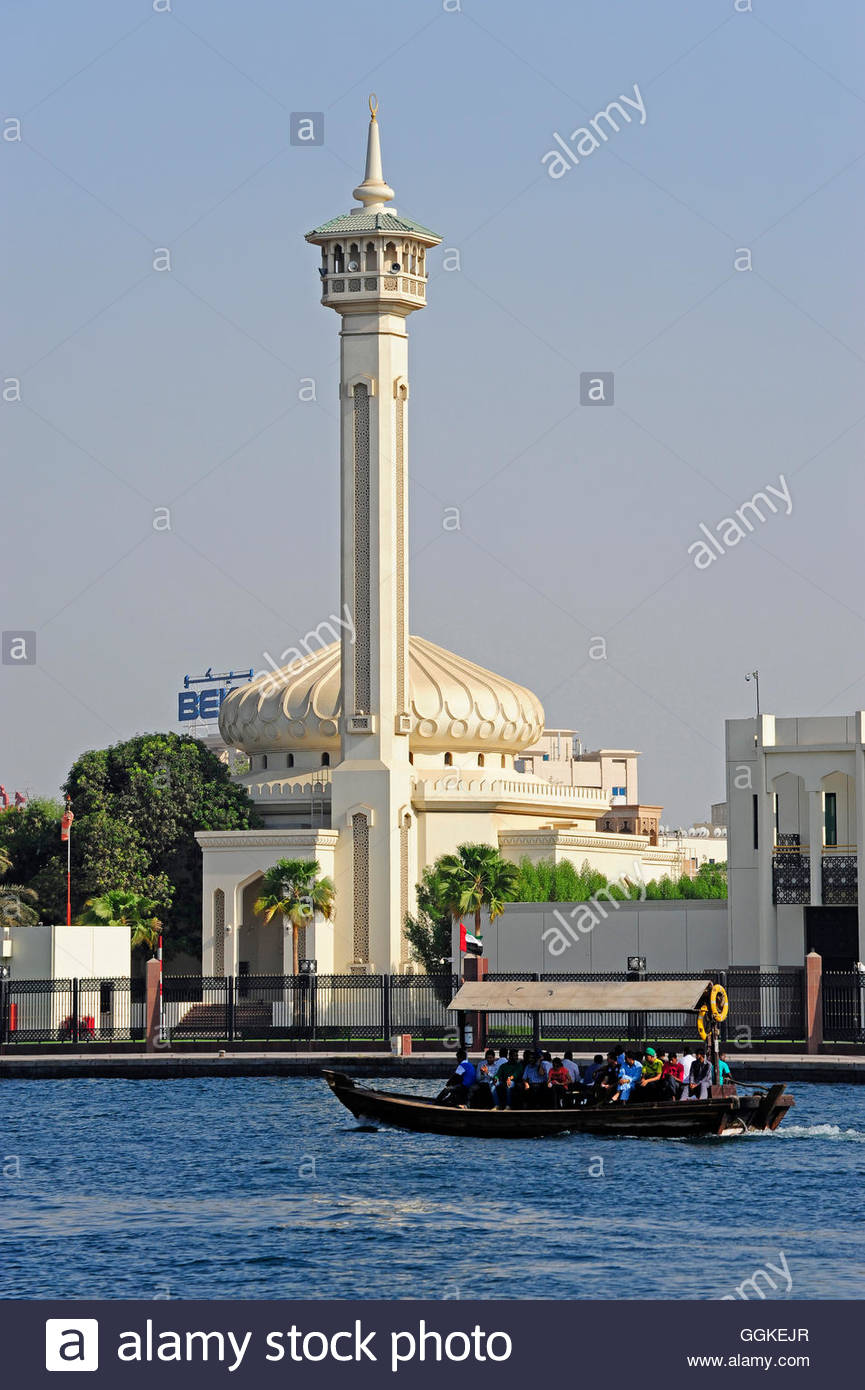 Boat on the Dubai Creek, behind it the minaret of Ruler's Court, Al Bastakiya, historic city centre, Dubai, - Stock Image