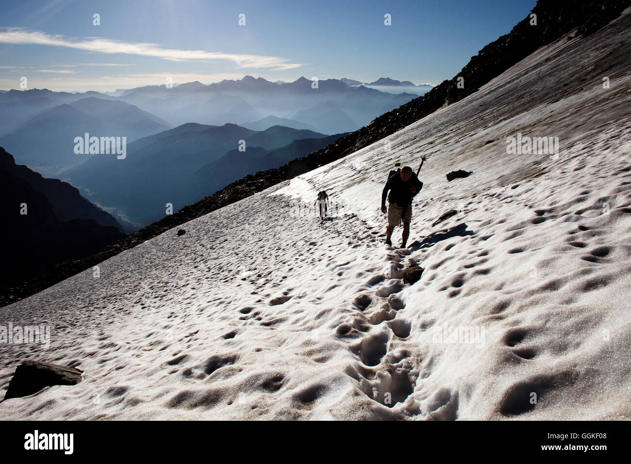 Two people hiking on a snowfield, ascend to Habicht (3277 m), Stubai Alps, Tyrol, Austria - Stock Image