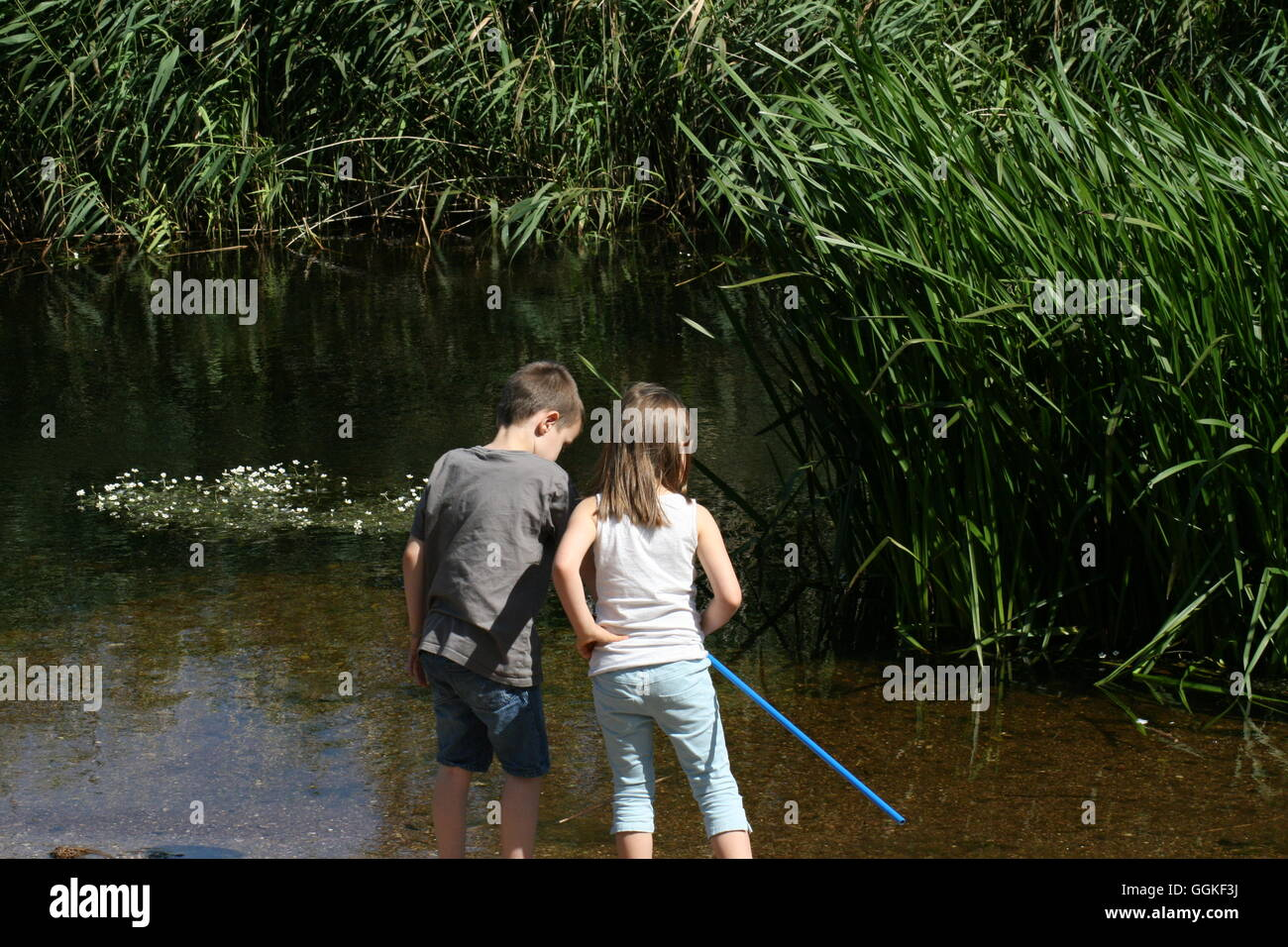 Brother and sister playing on river bank - Stock Image