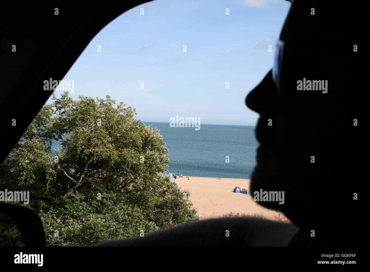 mans silhouette in car window with beach scene in the background - Stock Image