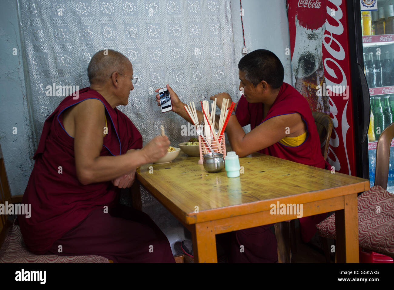 Two Buddhist monks watching a car model on the screen of a phone in a restaurant of  Dharamsala,  India. © - Stock Image