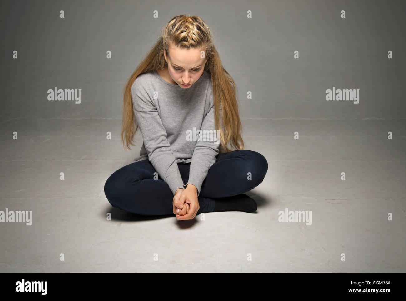 Sad young woman sitting in empty room on floor legs crossed hands tightly clasped in front looking down - Stock Image