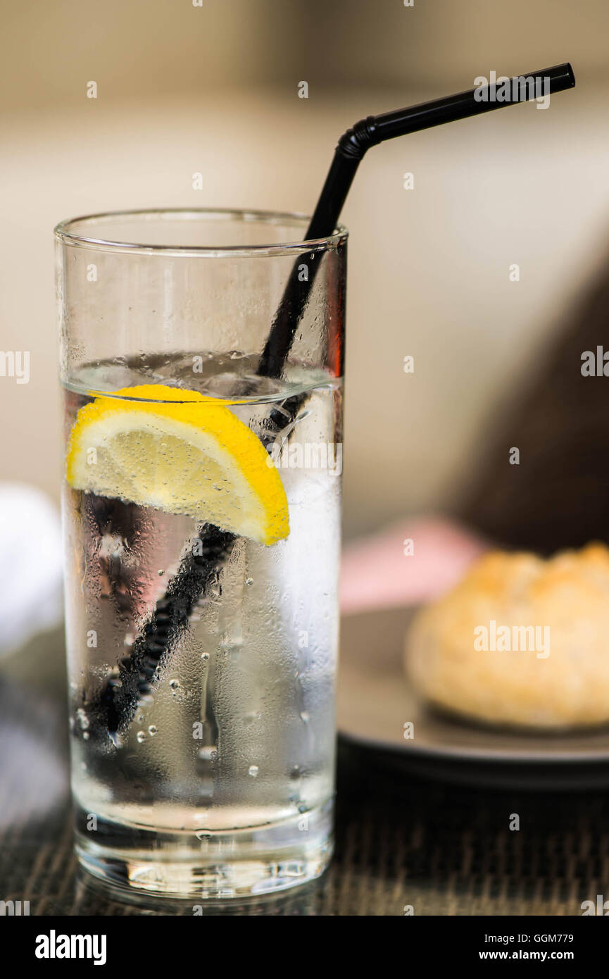Glass of Iced Still Water With a Straw Ice and Slice of Lemon - Stock Image