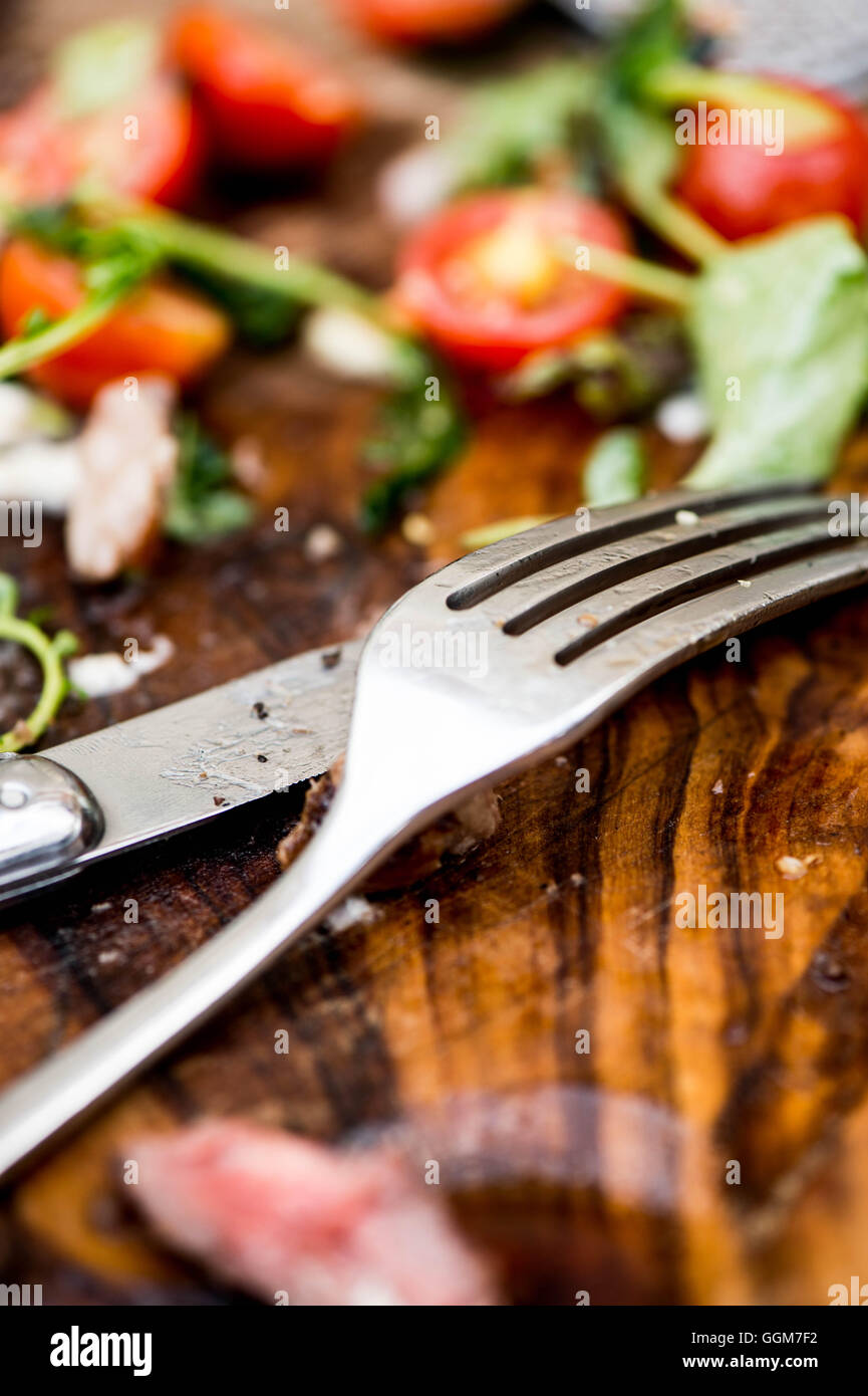 Finished Meal on a Wooden Board With a Knife and Fork - Stock Image