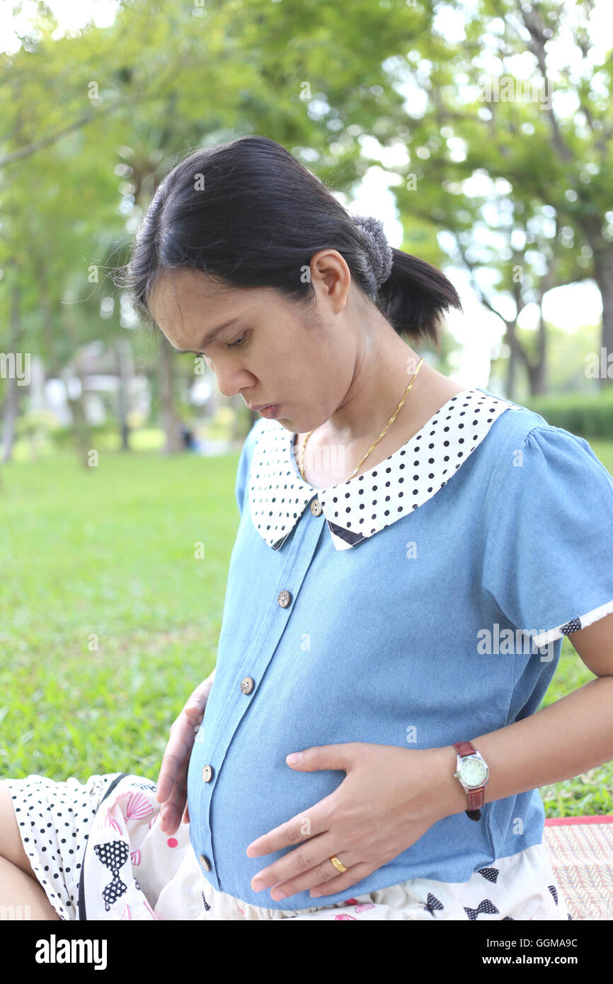Pregnant women there are suspicions that the baby in belly does not squirming in the public park. - Stock Image