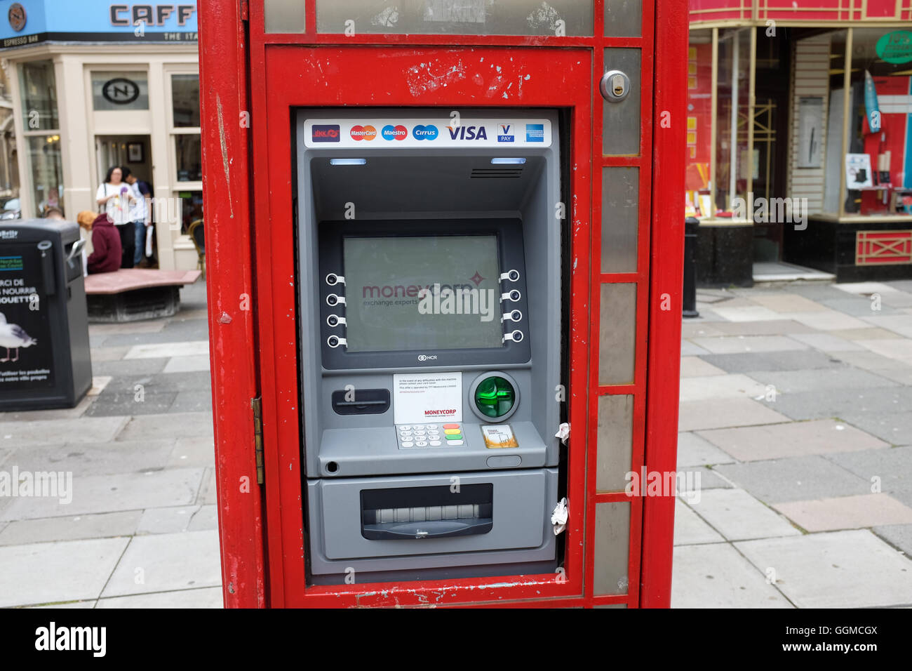 A traditional red phone box in England converted into a cash machine. - Stock Image