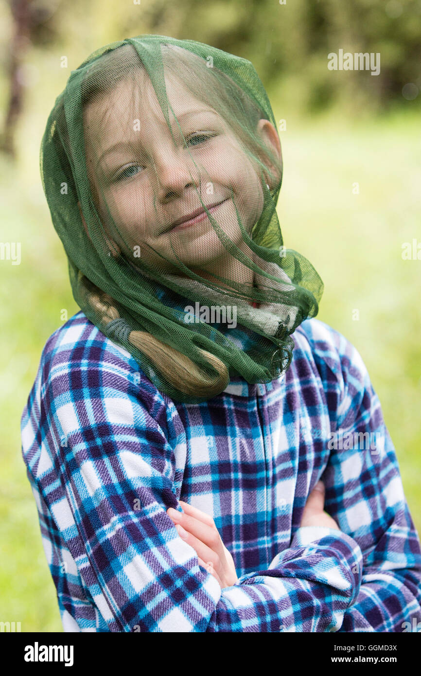 A girl protecting herself with a mosquito net against Black Flies, Fjordland, South Island, New Zealand - Stock Image