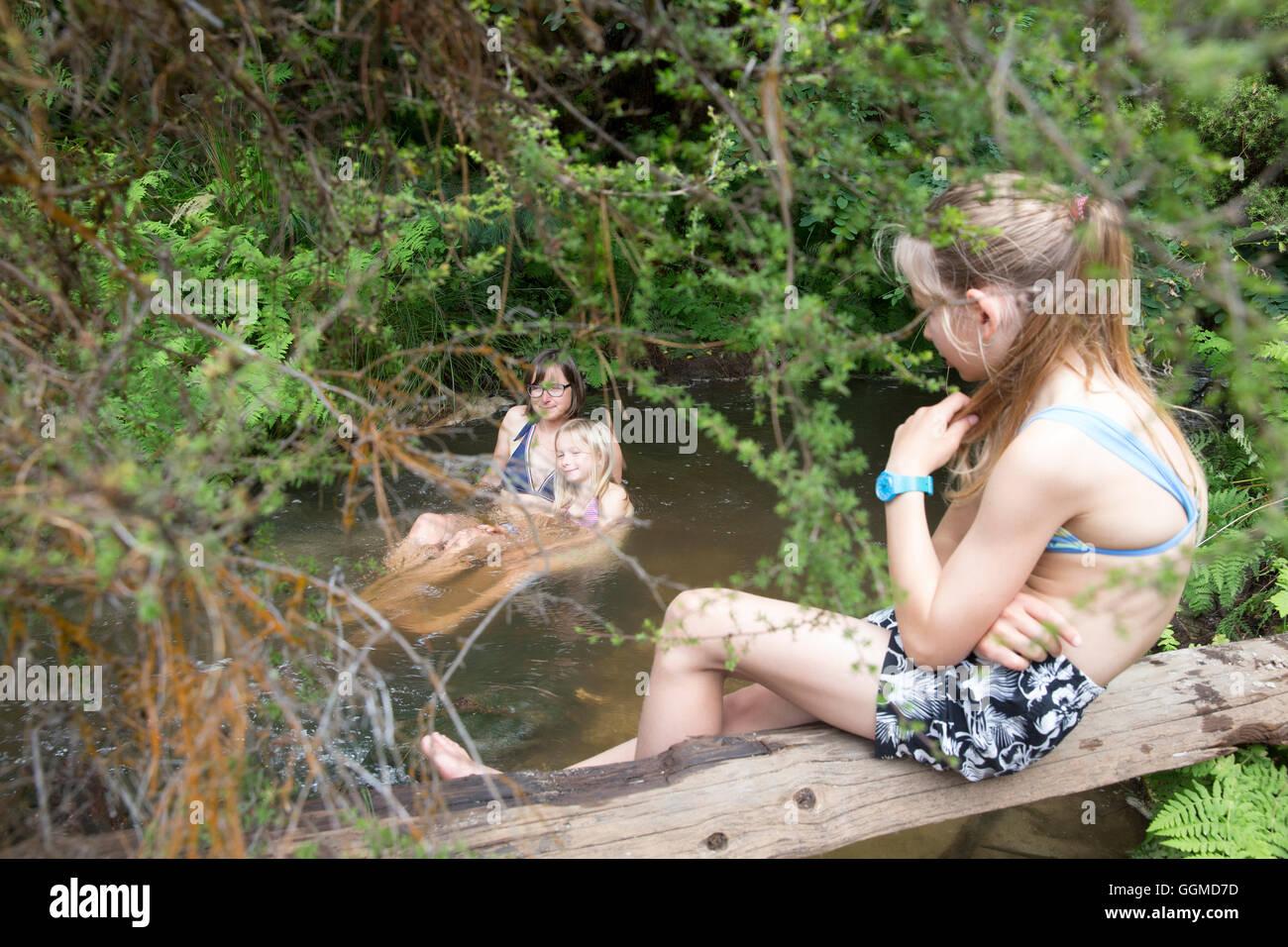 Taking a bath in the thermal river, Kerosene Creek, close to Rotorua, North Island, New Zealand - Stock Image