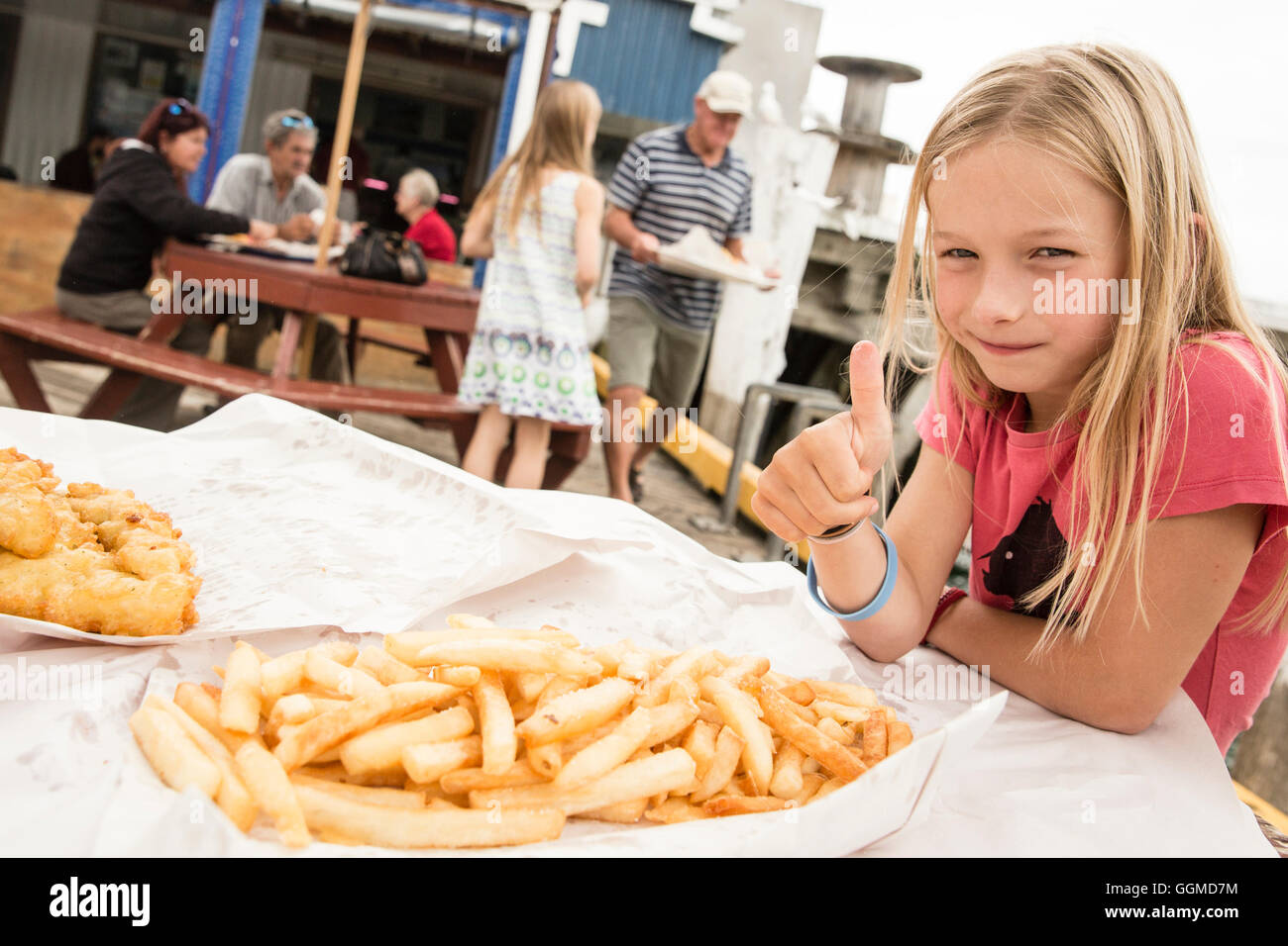 A girl with fish and chips at Tauranga, North Island, New Zealand - Stock Image
