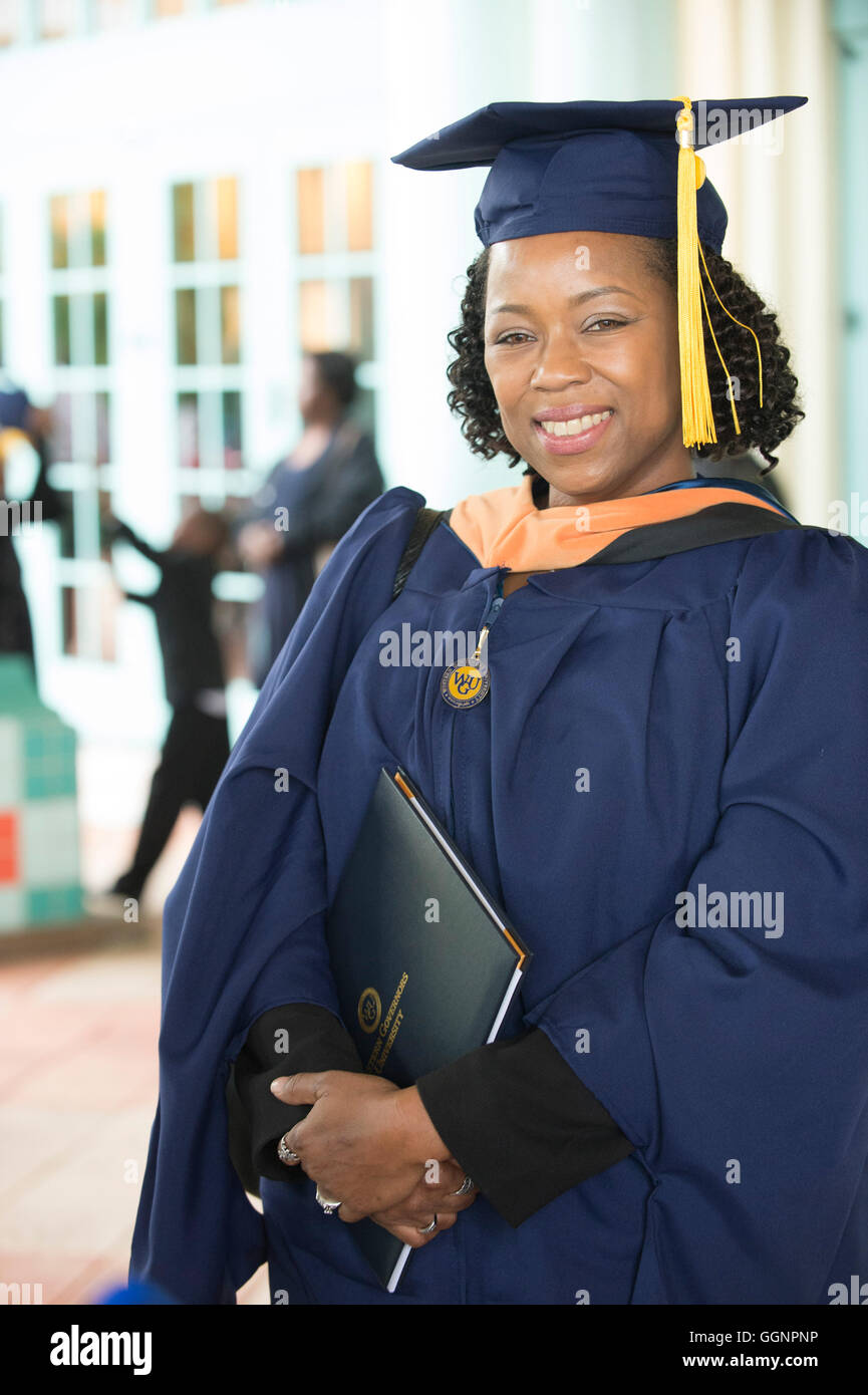 Graduate of Western Governors University poses with diploma after commencement ceremony in Orlando, Florida. - Stock Image