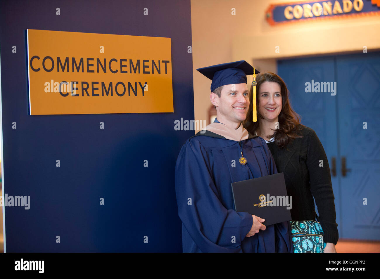 Graduate of Western Governors University poses with friend after commencement ceremony in Orlando, Florida. - Stock Image