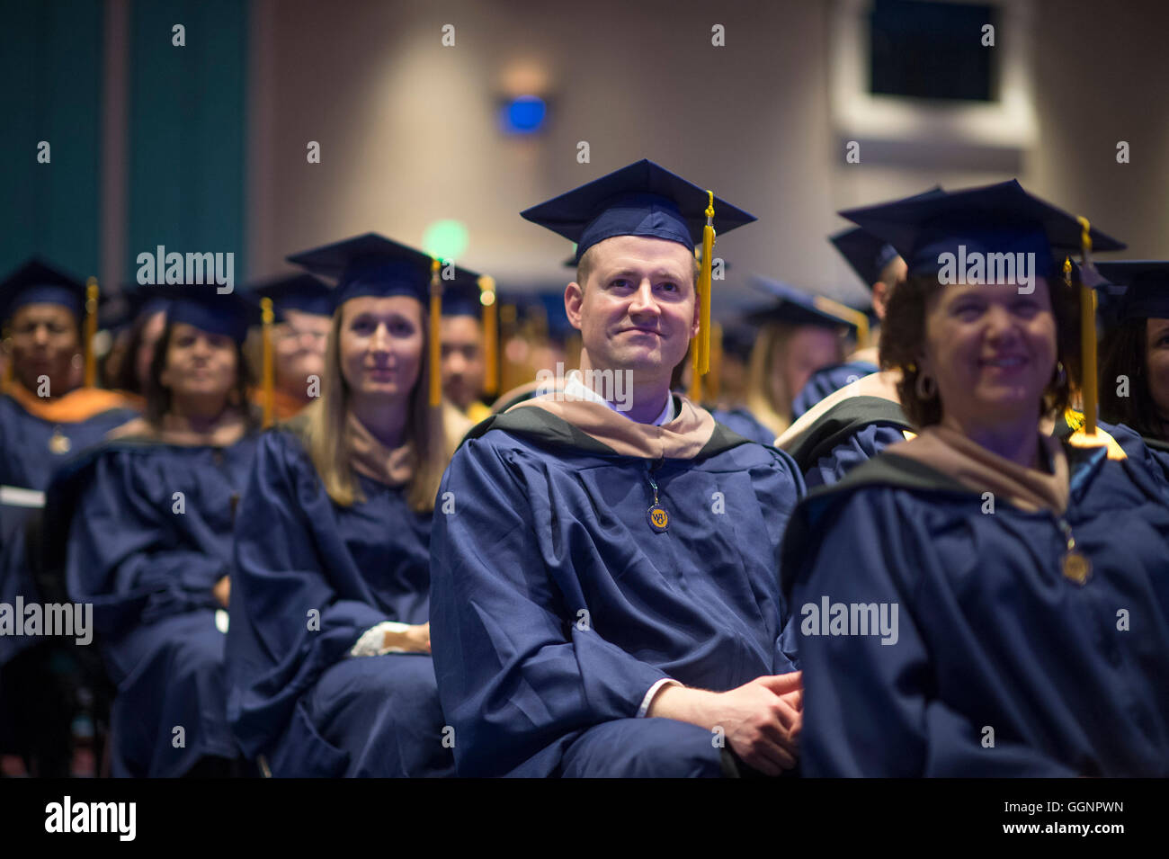 Graduation candidates in caps and gowns wait to receive diplomas at Western Governors University commencement ceremony - Stock Image