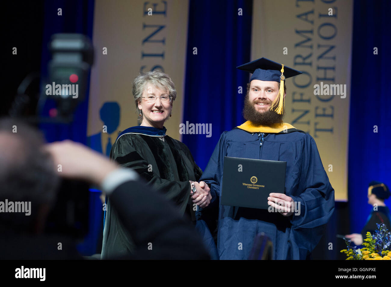 Graduation candidate in cap and gown receives diploma at Western Governors University commencement ceremony in Orlando, - Stock Image