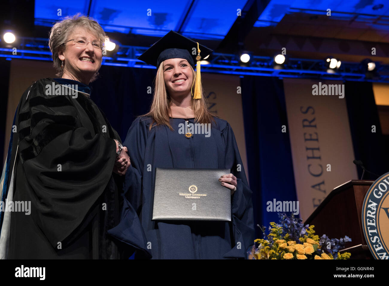 Student pose with diploma during commencement ceremony for Western Governors University, a fully accredited online - Stock Image