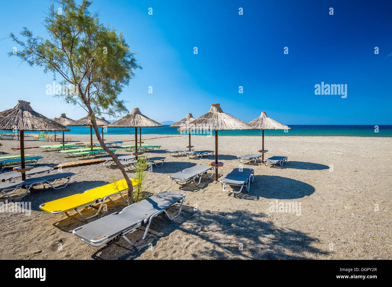 Straw umbrella on a sandy beach in Greece. Beach chairs with umbrellas on a beautiful beach in Crete island. Stock Photo
