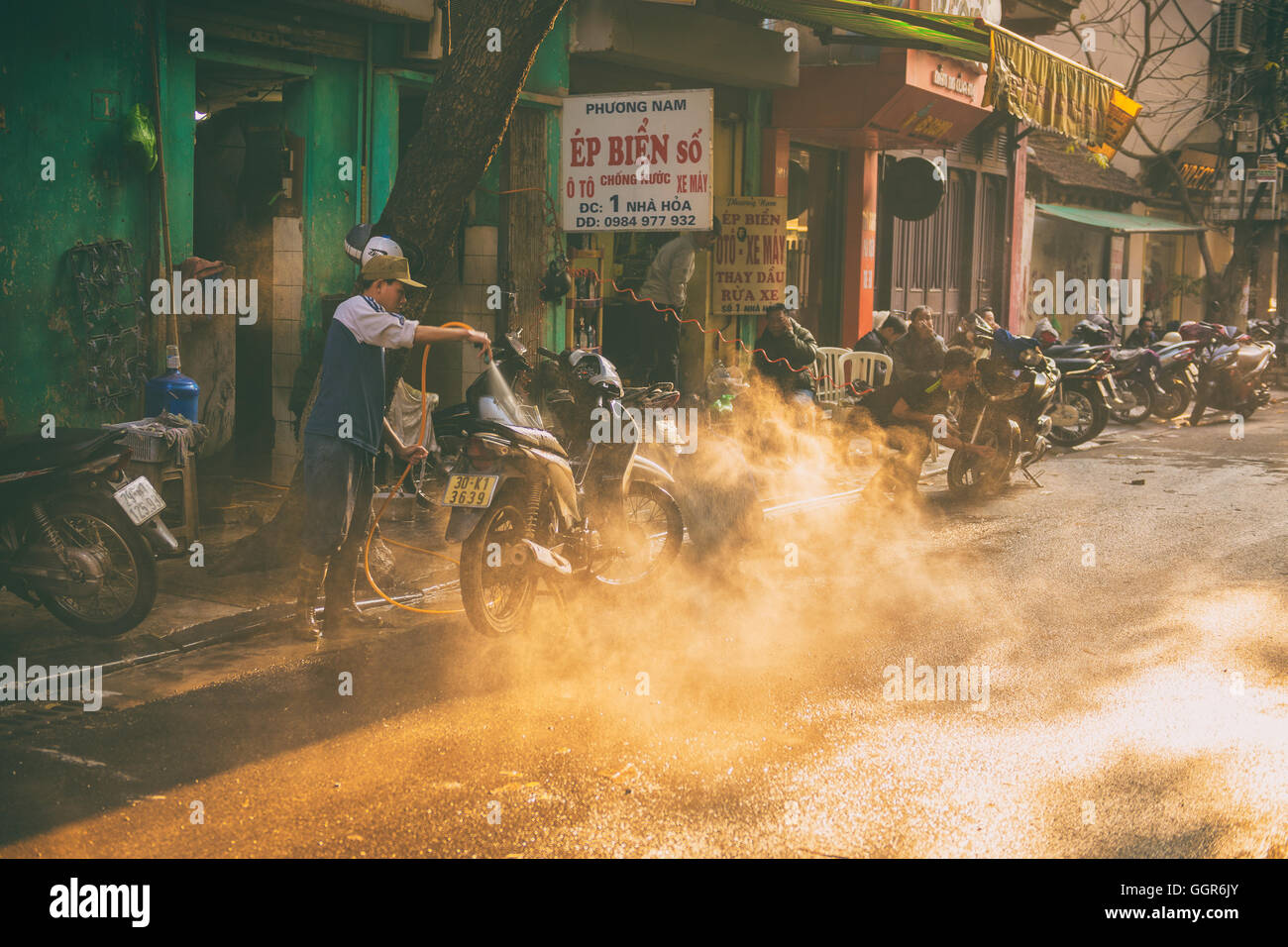 Hanoi, Vietnam - January 13, 2015 - The man washing the motorcycle in the afternoon day - Stock Image