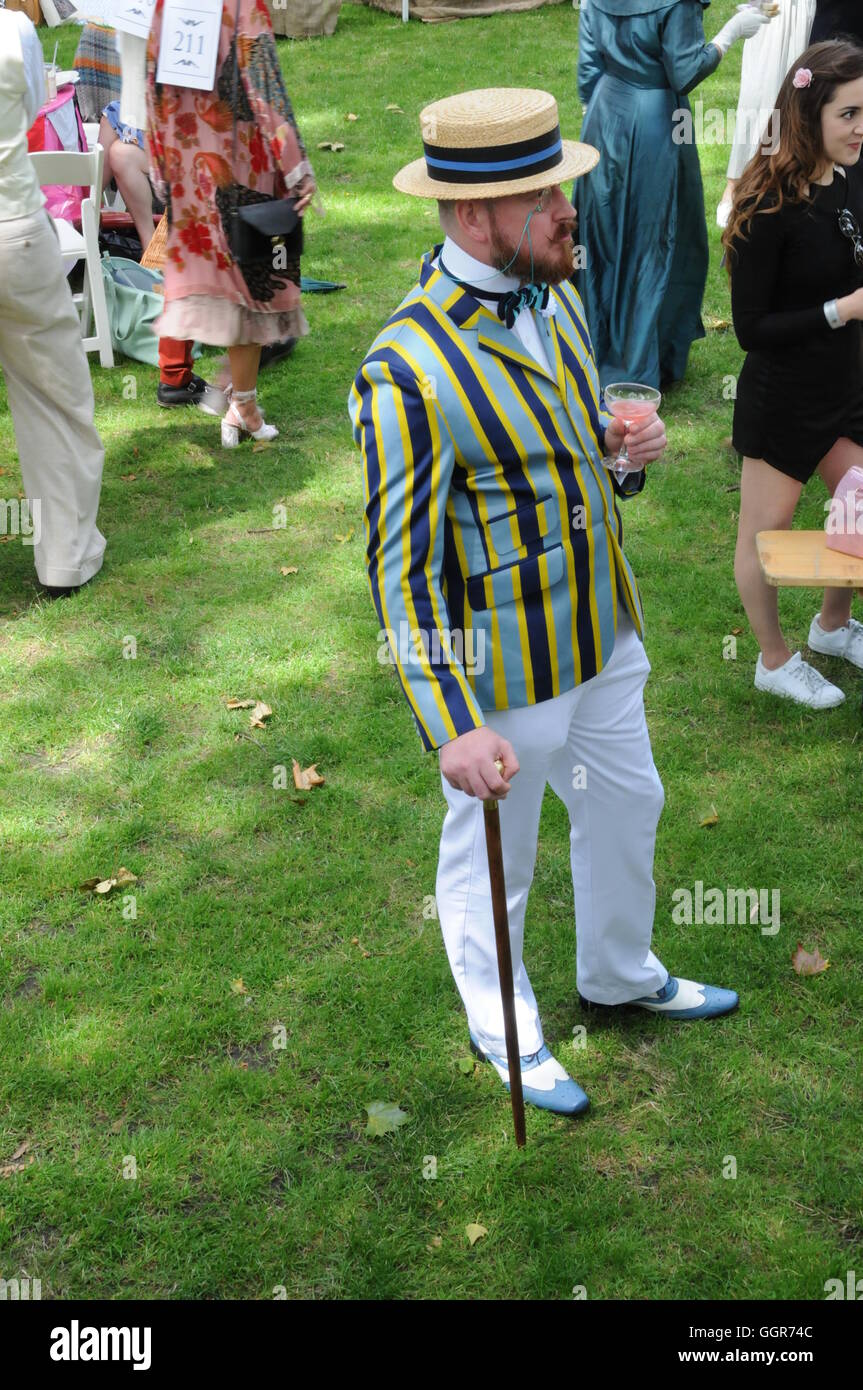 A man wearing a straw boater hat and striped blazer. - Stock Image