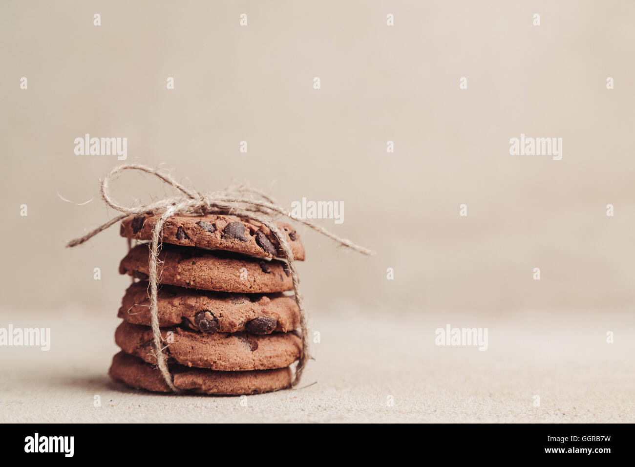Stacked chocolate chip cookies on grey table - Stock Image