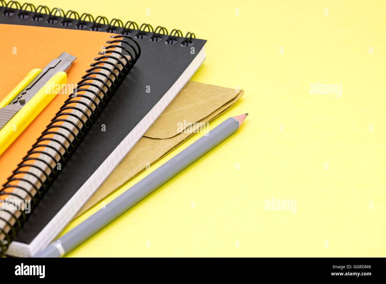 yellow writing desk background with colorful notebooks, pencil, envelope and letter opener - Stock Image