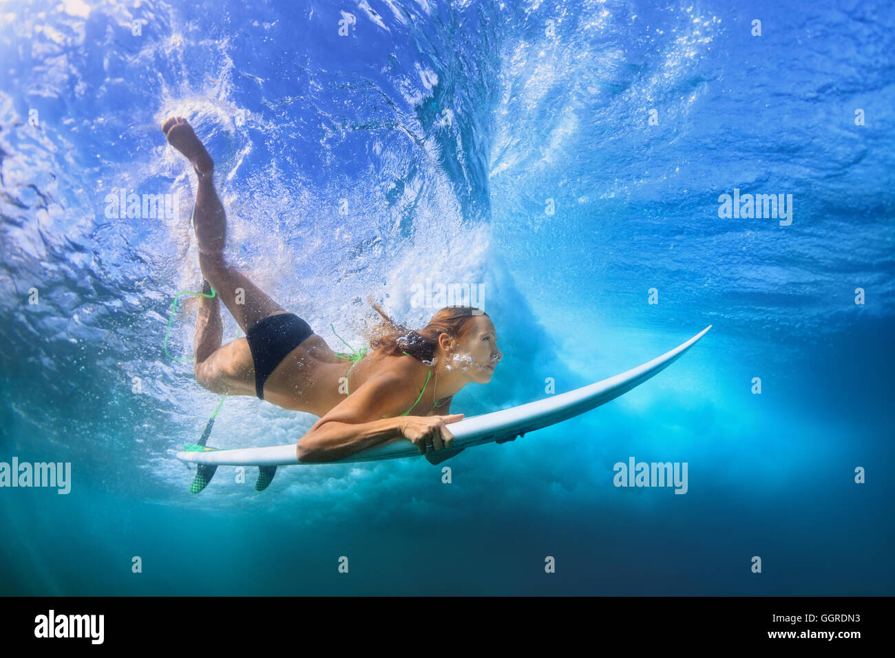 Young active girl in bikini in action - surfer with surf board dive underwater under breaking big ocean wave. school - Stock Image