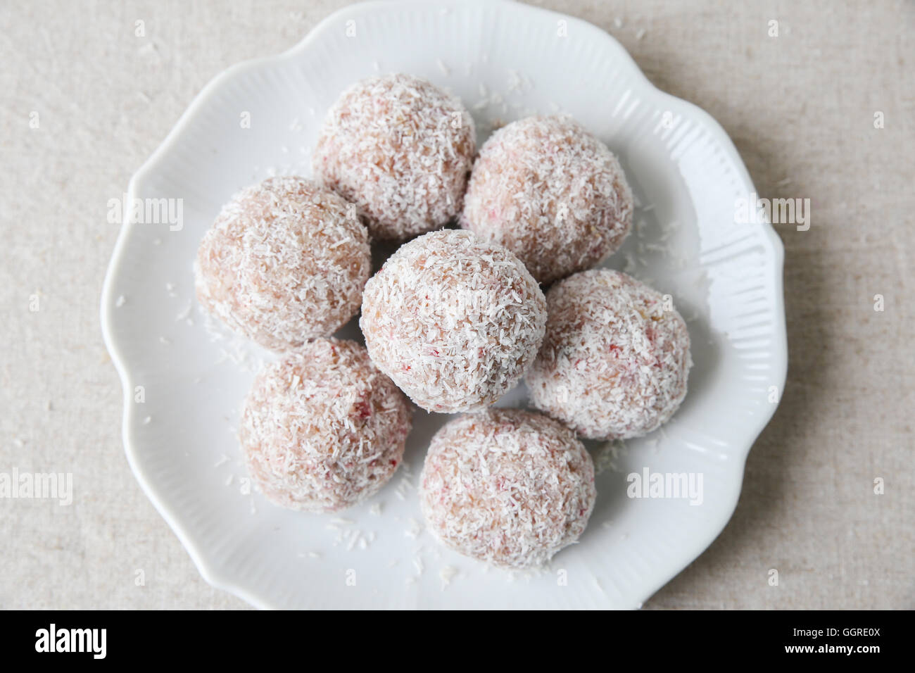 Homemade strawberry, date, cashew and coconut bliss ball on vintage plate - Stock Image