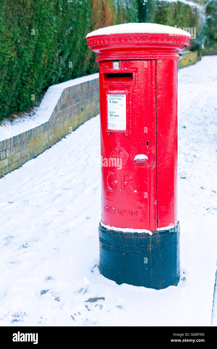 An English post box in a snowy winter - Stock Image